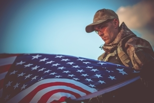 Soldier With American Flag Against Skyの写真素材 [FYI04384226]