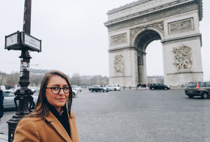 Portrait Of Young Woman Smiling While Standing Against Arc De Triompheの写真素材 [FYI04386565]
