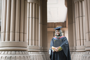 Portrait Of Smiling Young Woman Wearing Graduation Gown At Universityの写真素材 [FYI04386681]