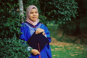 Smiling Young Woman Wearing Graduation Gown In Forestの写真素材 [FYI04386908]