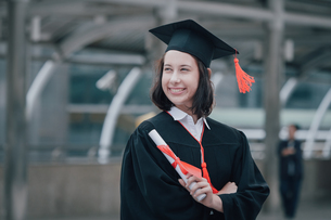 Smiling Young Woman In Graduation Gown Standing Outdoorsの写真素材 [FYI04391433]