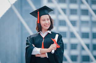 Young Woman Wearing Graduation Gown While Standing Against Office Buildingの写真素材 [FYI04391434]