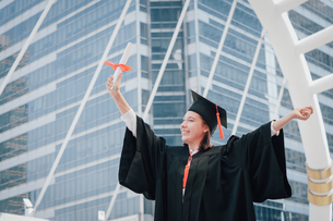 Happy Young Woman Wearing Graduation Gown While Standing Against Office Buildingの写真素材 [FYI04391442]