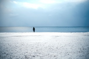 Person Standing On Snow Covered Beach Against Cloudy Skyの写真素材 [FYI04394736]
