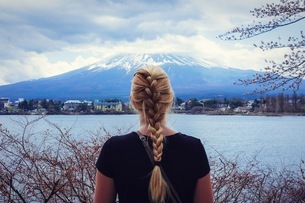 Rear View Of Woman With Braided Blond Hair In Front Of Mount Fuji And Riverの写真素材 [FYI04395071]