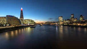 Thames River Amidst Illuminated Buildings In Cityの写真素材 [FYI04395743]