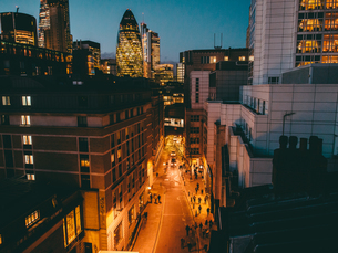 Illuminated City Street Amidst Buildings By 30 St Mary Axe At Duskの写真素材 [FYI04399831]