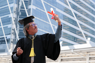 Businessman In Graduation Gown Clenching Fists Against Office Buildingの写真素材 [FYI04408121]