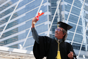 Businessman In Graduation Gown Clenching Fists Against Office Buildingの写真素材 [FYI04410436]