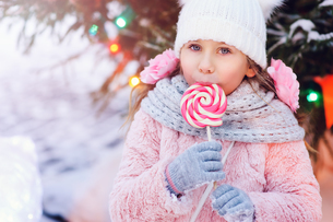 Portrait Of Cute Girl Eating Candy During Winterの写真素材 [FYI04411957]