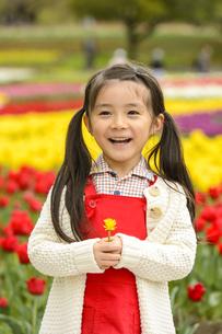 チューリップ畑の前で立つ女の子の写真素材 [FYI04412908]
