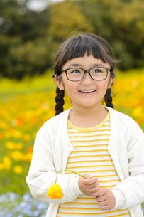 ポピー畑の前に立つメガネをかけた女の子の写真素材 [FYI04413641]