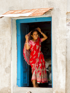 Portrait Of Smiling Woman Wearing Sari At Doorway In Villageの写真素材 [FYI04413725]