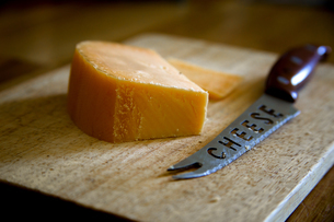 Close-up Of Knife With Cheese On Cutting Board At Tableの写真素材 [FYI04413929]