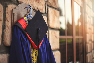 Graduation Gown With Mortarboard Hanging On Wallの写真素材 [FYI04414097]