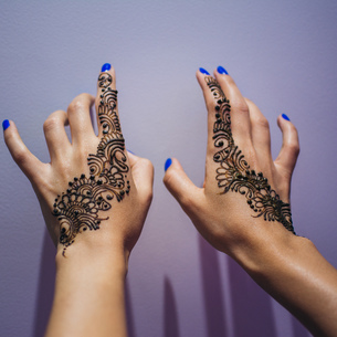 Cropped Hands Of Woman With Henna Tattoo By Wallの写真素材 [FYI04414508]