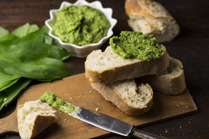 Close-up Of Bread With Green Paste And Leaves On Wooden Tableの写真素材 [FYI04414569]