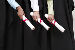 Midsection Of Female Friends Holding Diplomas During Graduationの写真素材 [FYI04416476]