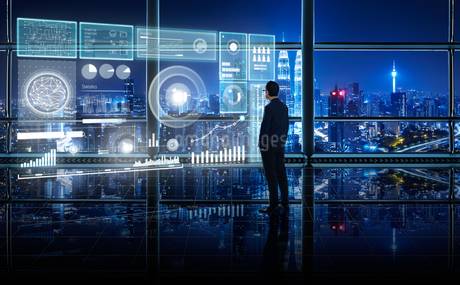 Digital Composite Image Of Businessman With Icons Working In Office At Nightの写真素材 [FYI04418113]