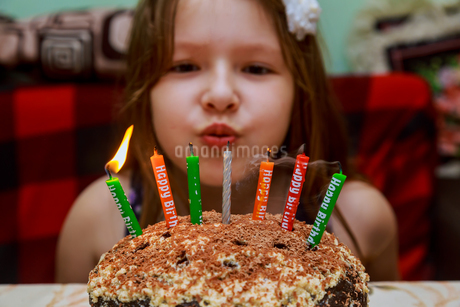 Close-up Portrait Of Smiling Girl Sitting By Cake At Homeの写真素材 [FYI04421593]