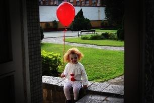 Girl In Spooky Costume Holding Red Balloon Seen Through Doorwayの写真素材 [FYI04421971]