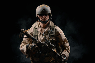 Man Wearing Helmet Holding Rifle Against Black Backgroundの写真素材 [FYI04422366]