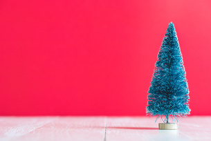Close-up Of Christmas Tree On Table Against Red Backgroundの写真素材 [FYI04422795]