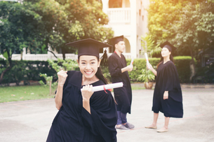 Cheerful Student With Clenched Fist Wearing Graduation Gownの写真素材 [FYI04423135]