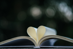 Close-up Of Papers In Heart Shape On Bookの写真素材 [FYI04423915]