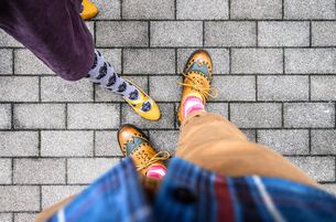Low Section Of Friends Standing On Footpathの写真素材 [FYI04425192]