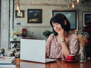 Smiling Young Woman Using Laptop On Table At Restaurantの写真素材 [FYI04425328]