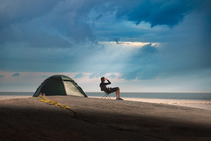Man Camping At Beach Against Cloudy Sky During Sunsetの写真素材 [FYI04426028]