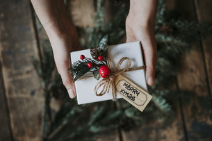 Cropped Hands Holding Christmas Present Over Hardwood Floorの写真素材 [FYI04426491]