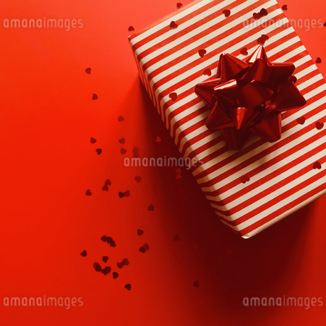 Directly Above Shot Of Gift Box And Heart Shape Confetti On Red Backgroundの写真素材 [FYI04427442]