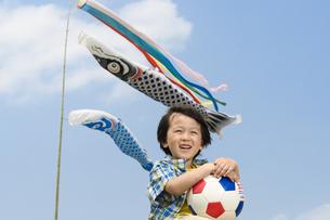 鯉のぼりの前に立つサッカーボールを持った男の子の写真素材 [FYI04428766]