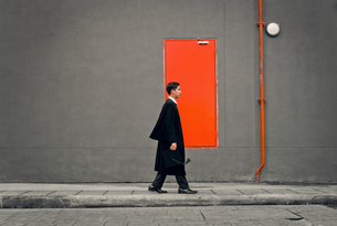 Profile View Of Young Man In Graduation Gown Walking By Gray Wallの写真素材 [FYI04429528]