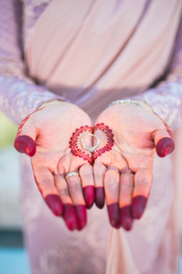 Midsection Of Bride With Henna Tattoo On Her Hands Holding Wedding Ringの写真素材 [FYI04430398]