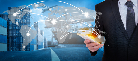 Digital Composite Image Of Businessman Operating Global Business At Factoryの写真素材 [FYI04430581]