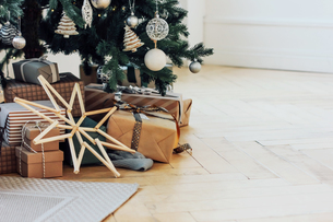 Christmas Tree By Gifts On Hardwood Floor At Homeの写真素材 [FYI04433458]