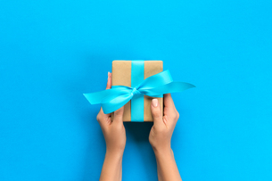 Cropped Hands Of Woman Holding Gift Box On Blue Backgroundの写真素材 [FYI04433566]