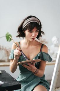 Female Painter Holding Palette And Paintbrush At Art Studioの写真素材 [FYI04434303]