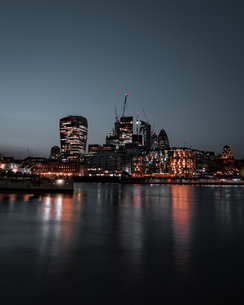 Illuminated Buildings By River Against Sky In City At Nightの写真素材 [FYI04434909]