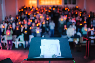 Microphones And Sheet Music On Stand Against People At Churchの写真素材 [FYI04436568]