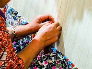 Cropped Image Of Hands Knitting Carpet Fabricの写真素材 [FYI04436603]