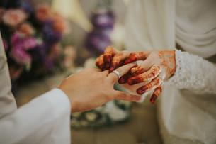 Close-up Of Bride Wearing Ring To Bridegroom During Weddingの写真素材 [FYI04436655]