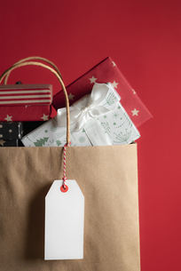 Close-up Of Gift Boxes In Paper Bag Against Red Backgroundの写真素材 [FYI04440792]