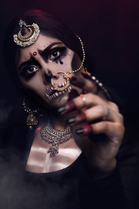 Close-up Of Young Woman In Traditional Clothing With Spooky Make-up Against Black Backgroundの写真素材 [FYI04441098]