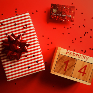 Directly Above Shot Of Gift Box With Credit Card And Wooden Calendar On Red Backgroundの写真素材 [FYI04442080]