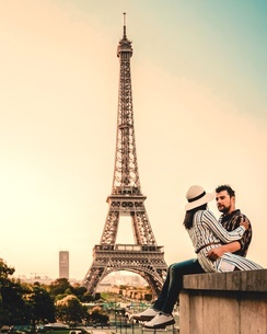 Couple Romancing While Sitting On Retaining Wall Against Eiffel Tower During Sunsetの写真素材 [FYI04442660]