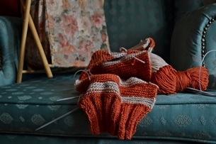 Close-up Of Wool And Knitting Needle On Sofaの写真素材 [FYI04445908]